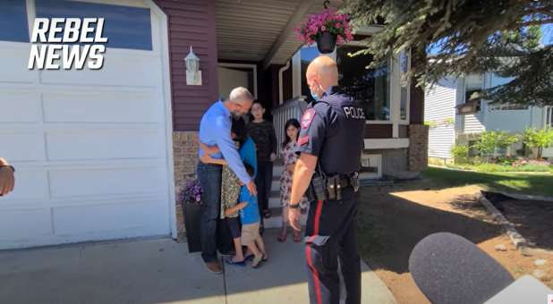 Pastor Tim Stephens hugging his children before being arrested outside his Alberta, Canada, home.