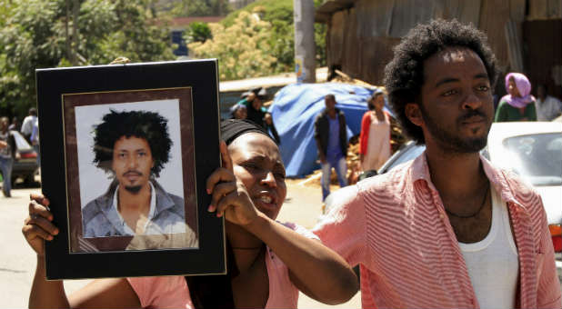 A woman holds a photo of a man said to be one of the 30 Ethiopians martyred by the Islamic State.