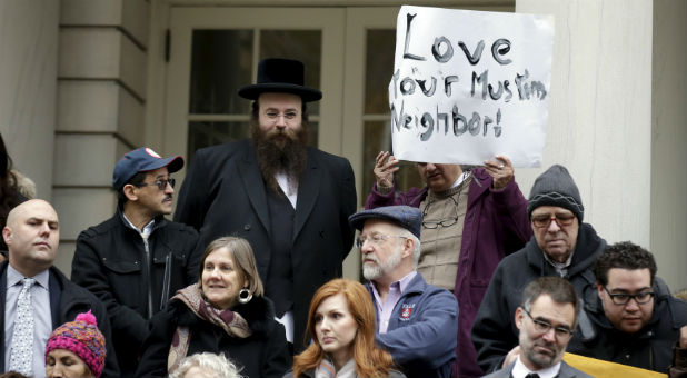 People opposed to Republican presidential Donald Trump's proposal to ban Muslims from entering the United States stand on the steps of New York's City Hall during an interfaith rally in Manhattan.