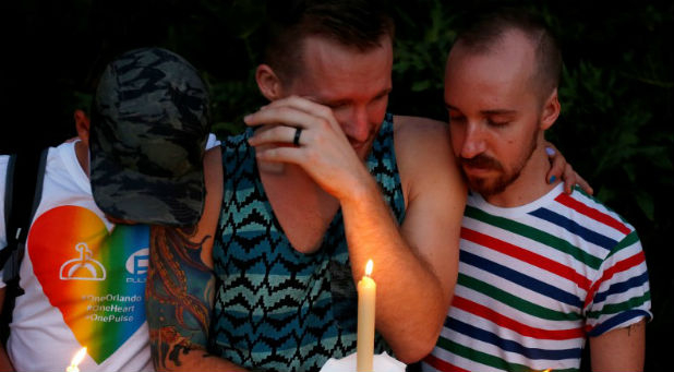 A man cries while his friends comfort him as they take part in a vigil for the Pulse night club victims following last week's shooting in Orlando