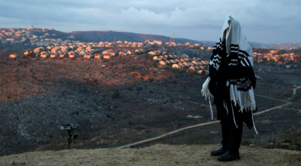 A Jewish man, covered in a prayer shawl, prays in the Jewish settler outpost of Amona in the West Bank December