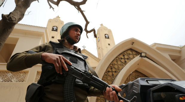 An armed policeman secures the Coptic church that was bombed on Sunday in Tanta, Egypt