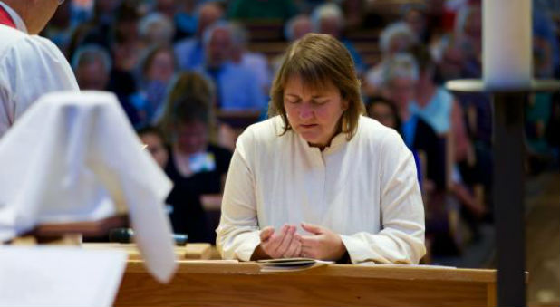 Bishop Karen Oliveto, the first openly gay bishop in The United Methodist Church, kneels during the consecration service held on July 16, 2016, at Paradise Valley United Methodist Church in Scottsdale, Arizona.