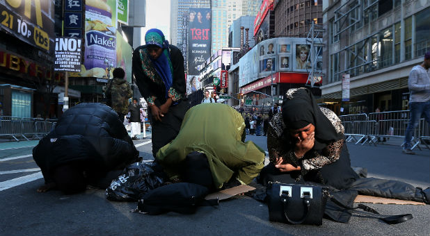 """Muslim women kneel on Broadway Ave. as they take part in afternoon prayers during an """"I am Muslim Too"""" rally in Times Square"""