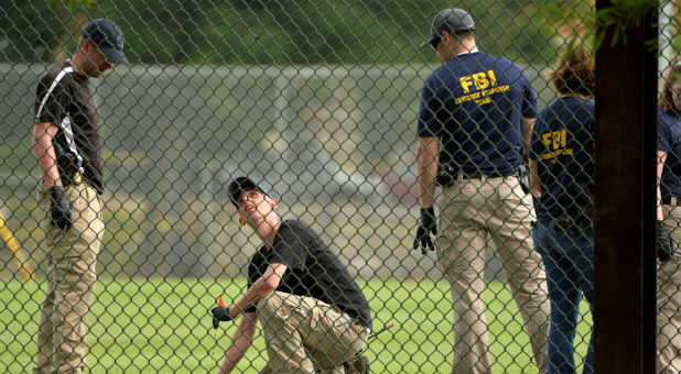 FBI technicians examine the outfield area of a baseball field for evidence where shots were fired during a Congressional baseball practice wounding House Majority Whip Steve Scalise, R-La., in Alexandria, Virginia.