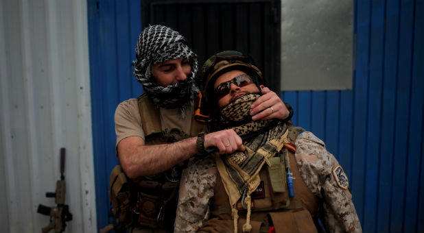 A player depicting an Islamic State militant holds a fake knife as he simulates a beheading of a player depicting a soldier from the U.S.-led coalition forces during an airsoft game.