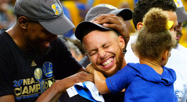 Golden State Warriors forward Kevin Durant and guard Stephen Curry celebrate with Curry's daughter Riley after defeating the Cleveland Cavaliers 129-120 in game five of the NBA Finals.