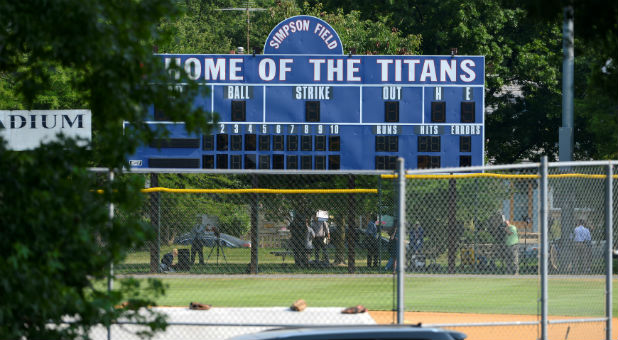 Investigators under a scoreboard search for clues at the scene where shots were fired during a congressional baseball practice, wounding House Majority Whip Steve Scalise, R-La., Alexandria, Virginia.