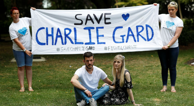 The parents of critically ill baby Charlie Gard, Connie Yates and Chris Gard, pose for photographers as supporters hold a banner before delivering a petition to Great Ormond Street Hospital, in central London, Britain.