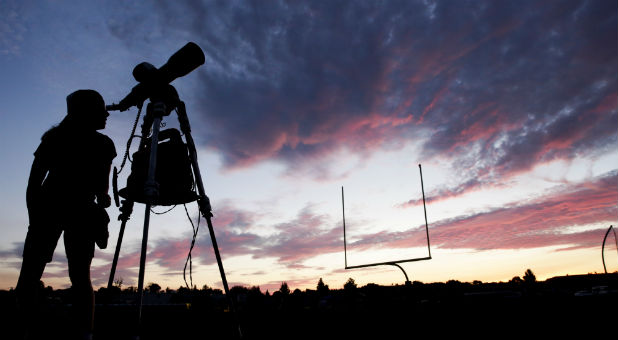 A woman looks through a telescope on the football field at Madras High School the evening before a solar eclipse in Madras, Oregon, U.S., Aug. 20, 2017.