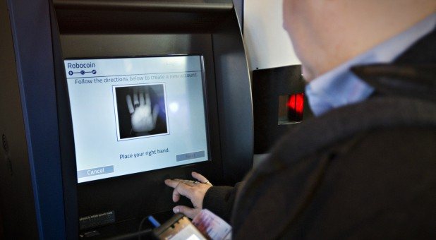 A customer registers his handprint before proceeding on the world's first-ever permanent bitcoin ATM.