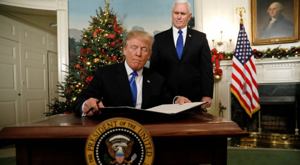 U.S. Vice President Mike Pence stands by as U.S. President Donald Trump signs a proclamation that states the United States recognizes Jerusalem as the capital of Israel and will move its embassy there.