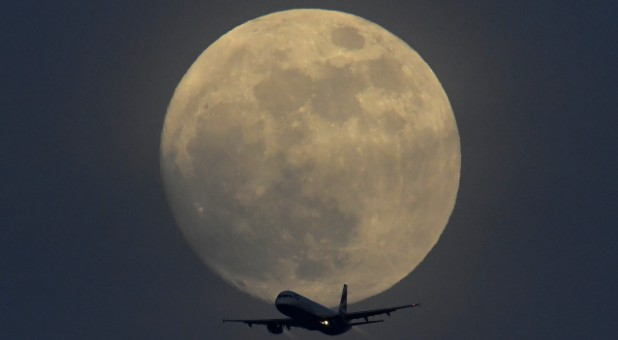 A British Airways aircraft flies in front of a full moon over London, England.