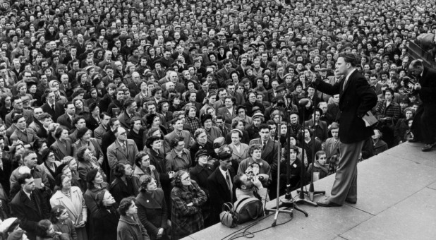 Billy Graham preaches at a crusade.