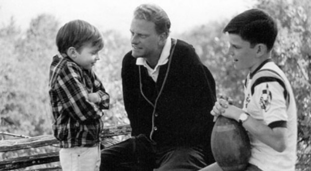 Billy Graham tried to save the world, traveling for months at a time to more than 170 countries to preach the gospel to tens of millions. In a rare moment at home in 1965, he spends time with sons Ned, left, and Franklin.