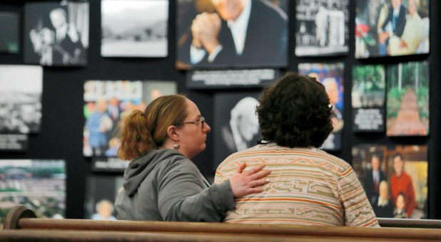 Mourners comfort each other as they sit in a pew near a display of pictures of evangelist Billy Graham, who died Wednesday at his Montreat home aged 99, at Chatlos Memorial Chapel on the grounds of the Billy Graham Training Center in Asheville, North Carolina.