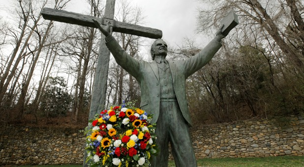 A garland sits under a large bronze statue of evangelist Billy Graham, who died Wednesday at his home aged 99, on the grounds of a Christian conference center in nearby Ridgecrest, North Carolina.