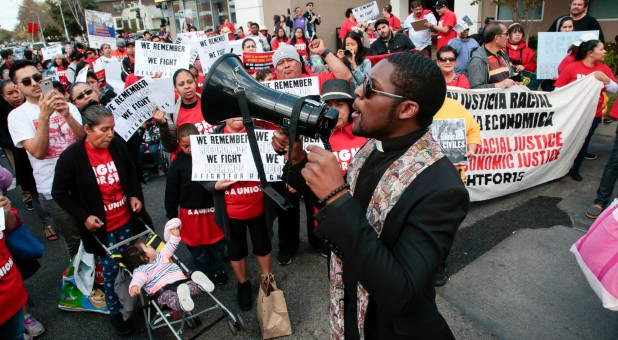 Pastor Eddie Anderson leads a chant with fast-food workers and supporters during a protest outside a McDonald's restaurant in Los Angeles, California.