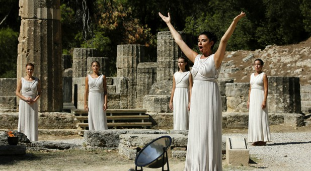 Greek actress Ino Menegaki, playing the role of high priestess, prays to the god Apollo before lighting a torch from the sun's rays reflected in a parabolic mirror during a dress rehearsal for the torch-lighting ceremony of the Sochi 2014 Winter Olympic Games at the site of ancient Olympia in Greece on Sept. 28, 2013.