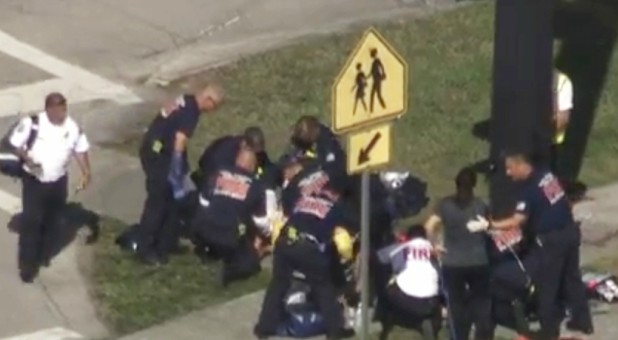 Rescue workers deal with a victim near Marjory Stoneman Douglas High School during a shooting incident in Parkland, Florida.