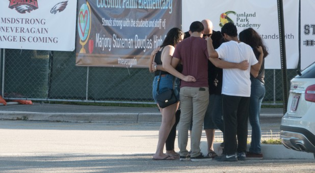 People gather for an impromptu prayer circle, in front of the building where the shooting took place, as students and parents attend a voluntary campus orientation at the Marjory Stoneman Douglas High School.