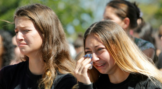 Students mourn during a community prayer vigil for victims of yesterday's shooting at nearby Marjory Stoneman Douglas High School in Parkland, at Parkridge Church in Pompano Beach, Florida.
