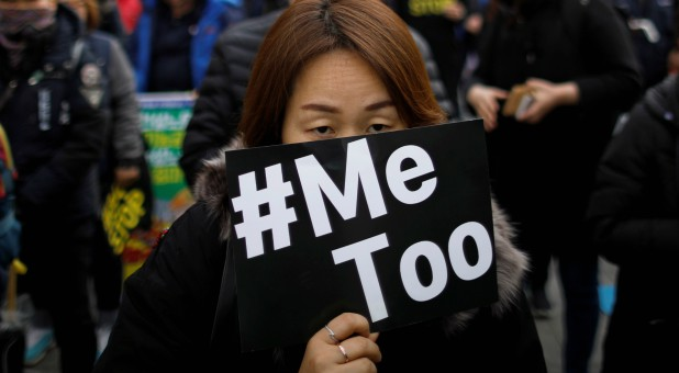 People attend a protest as a part of the #MeToo movement.