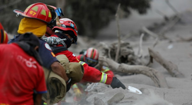 A firefighter shovels ashes while searching for bodies at an area affected by the eruption of the Fuego volcano in the community of San Miguel Los Lotes in Escuintla, Guatemala.