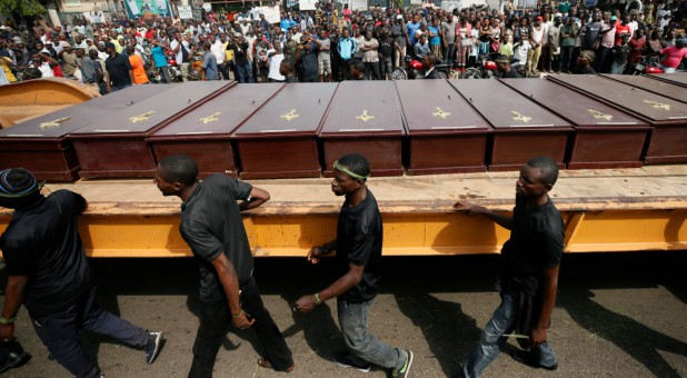 Men march along the truck carrying the coffins of people killed by the Fulani herdsmen, in Makurdi, Nigeria, January 11, 2018.