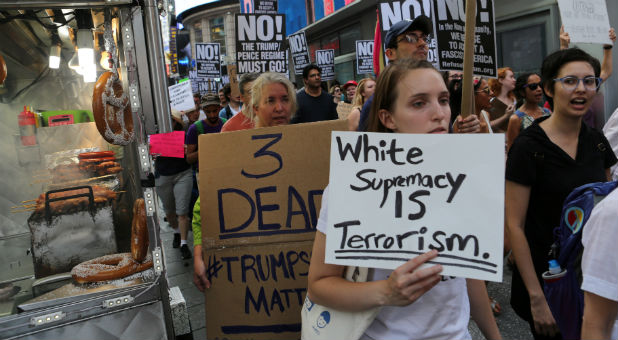 "A protester holds a sign reading ""White supremacy is terrorism"" at a march against white nationalism in New York City, the day after the attack on counter-protesters at the ""Unite the Right"" rally organized by white nationalists in Charlottesville, Virginia."