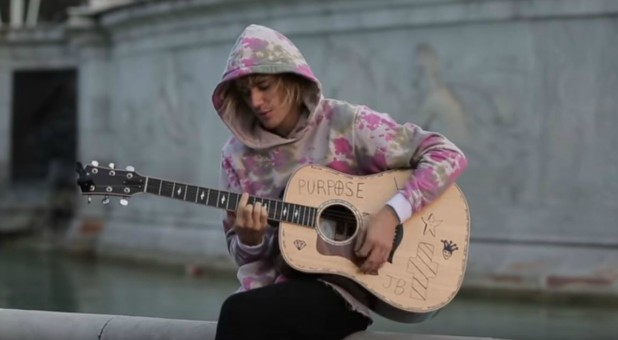 Justin Bieber plays the guitar outside Buckingham Palace.