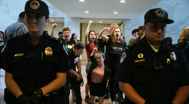 Protesters demonstrate against Judge Brett Kavanaugh's nomination to the U.S. Supreme Court in the atrium of the Hart Senate Office Building.