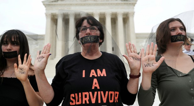 Women stand in silent protest outside the U.S. Supreme Court building after the U.S. Senate voted to confirm the Supreme Court nomination of Judge Brett Kavanaugh on Capitol Hill.