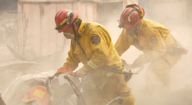 Cal Fire firefighters comb through a house destroyed by the Camp Fire in Paradise, California.