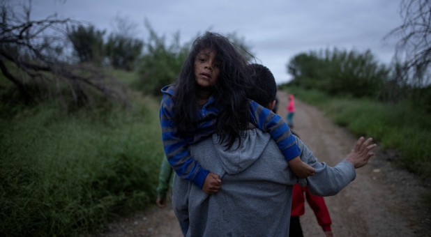 A migrant man races down a dirt path holding a girl after illegally crossing the Rio Grande River into the United States from Mexico, in Fronton, Texas.