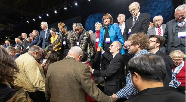 Delegates and bishops join in prayer at the front of the stage before a key vote on church policies about homosexuality during the 2019 United Methodist General Conference in St. Louis.