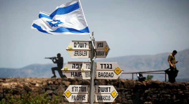 An Israeli soldier stands next to signs pointing out distances to different cities, on Mount Bental, an observation post in the Israeli-occupied Golan Heights that overlooks the Syrian side of the Quneitra crossing, Israel.