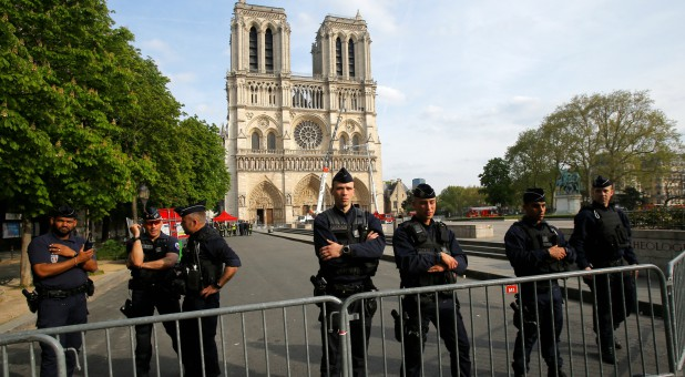 Police officers stand behind the security barriers in front of Notre Dame Cathedral.