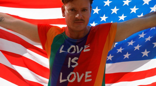 Gilson from Germany poses with an American flag as he participates in the Gay Pride parade along Paulista Avenue in Sao Paulo, Brazil.